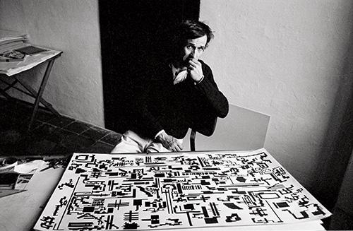 Alighiero Boetti davanti alla Storia naturale della Moltiplicazione nel suo studio a Trastevere, foto di Gianfranco Gorgoni